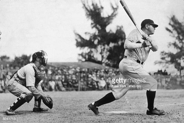 Profile of American baseball player Babe Ruth swinging at bat as a catcher crouches behind him during a game