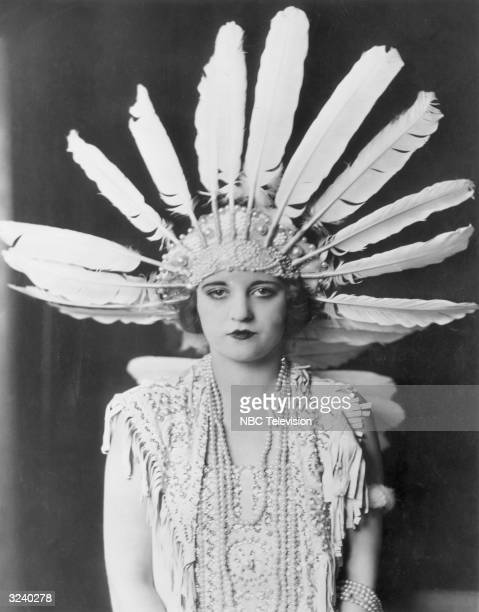 Promotional studio portrait of American actor Tallulah Bankhead wearing a large feather headdress and beaded necklaces, with a dark backdrop.