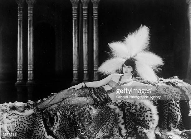Silent screen actress Betty Blythe reclines on a bed of furs to display a risque costume of sequins and feathers