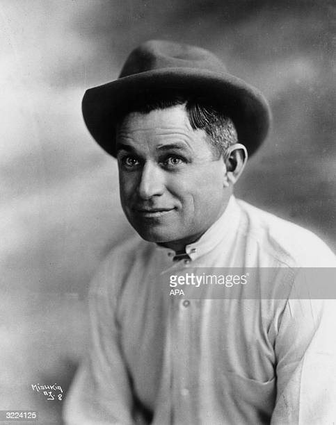 Studio portrait of American entertainer Will Rogers wearing a white shirt and a hat