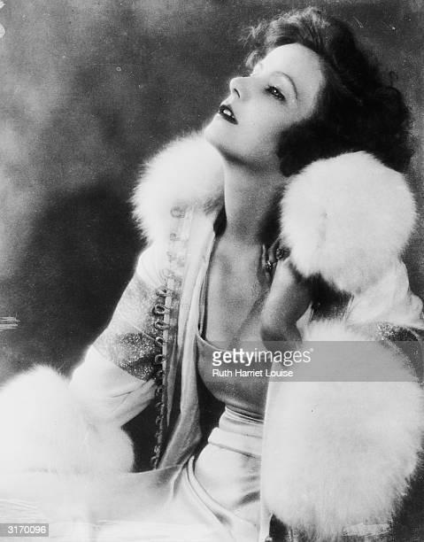 Swedish born American actress Greta Garbo wearing a long dress and fur trimmed coat.