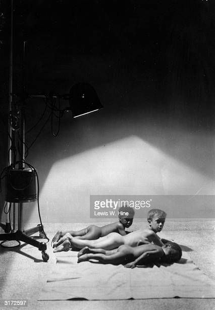 Three nude young boys of different races lay stomachdown on towels beneath a sun lamp