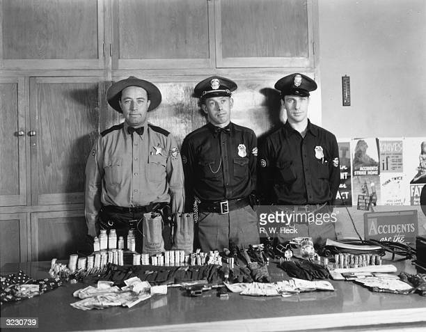 Three uniformed police officers pose behind a table of captured money weapons and narcotics from a bank robbery in Harney county Oregon 1920s Glen...