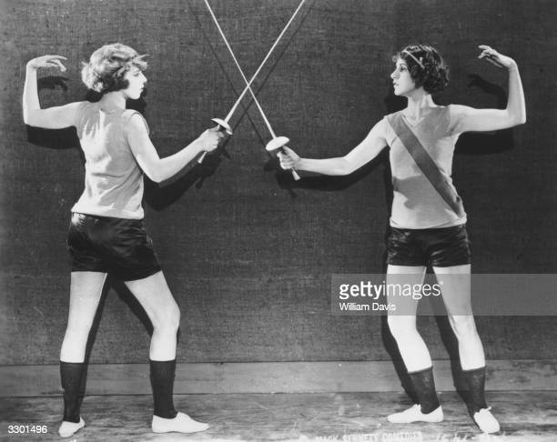Two female fencers with foils crossed ready to start