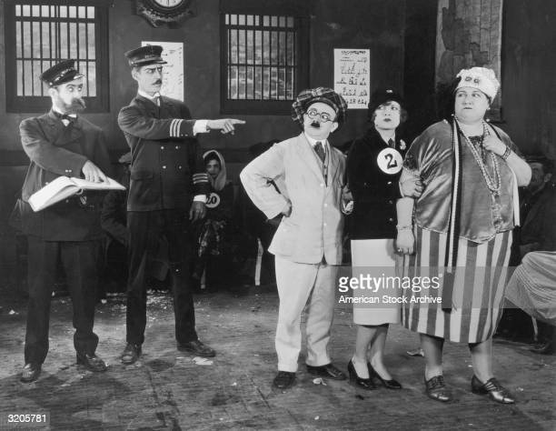 Two police officers point at a man and two women standing in a lineup inside a police station in an unidentified silent film still from a Mack...