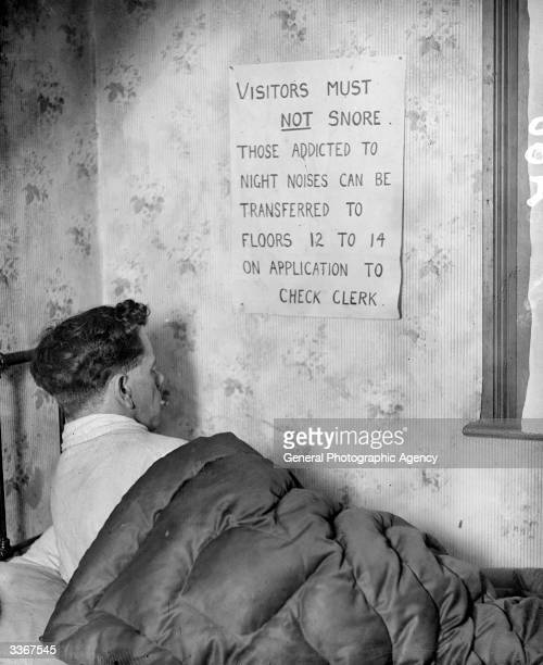 A handwritten sign tacked onto the wall of a grubby hotel room warns the occupant that snoring is forbidden