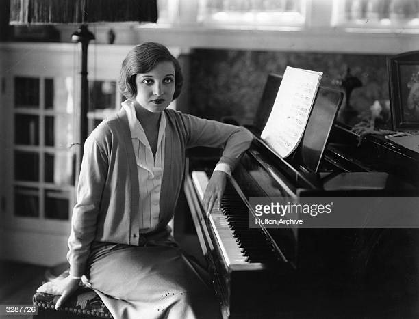 Alice Joyce, the Hollywood actress, at home playing her piano.