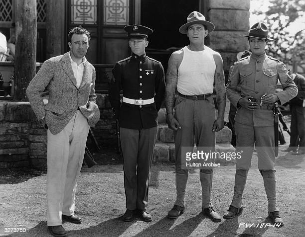 American director Raoul Walsh poses with his stars Victor McLaglen and Edmund Lowe right during production of the Fox film 'What Price Glory'