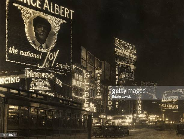 Automobiles and a streetcar pass illuminated theater marquees and billboards at night in Times Square New York City