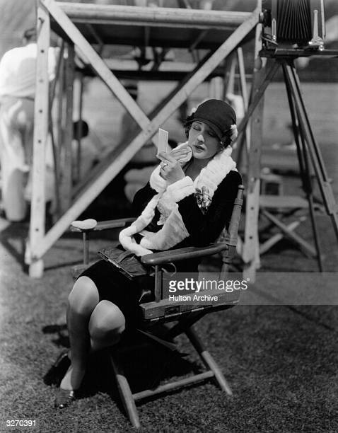 Dolores Costello the American silent screen heroine who worked for Warner Brothers She is outside on location applying powder to her face between...