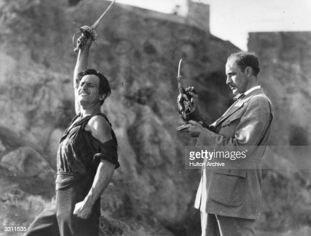 Douglas Fairbanks Senior in character for the film 'The Black Pirate', alongside an artist who is making a model of him.