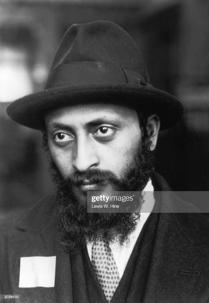 Headshot of a bearded Armenian Jewish man wearing a hat, suit and numbered immigrant tag, Ellis Island, New York City.