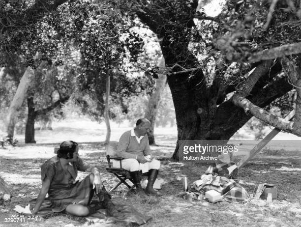 Lillian Gish and Norman Kerry are currently filming 'Annie Laurie' directed by Canadian John S Robertson They are all having a picnic lunch whilst on...