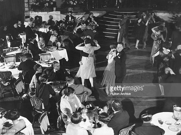 People dancing and dining at London's Palm Beach Cafe on the bank of the River Thames