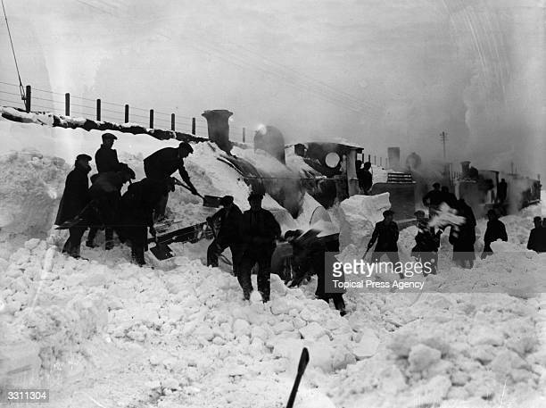 A locomotive snow plough being dug out of deep snow in Amesbury Wiltshire