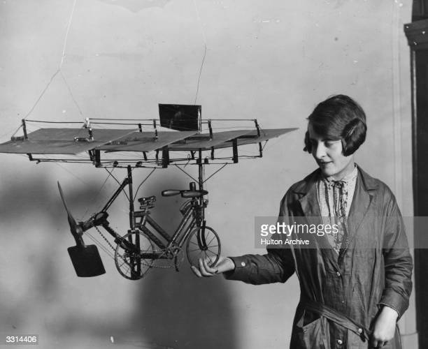 A woman holding a model of a pedal cycle fitted with wings which was on exhibition at Central Hall Westminster London