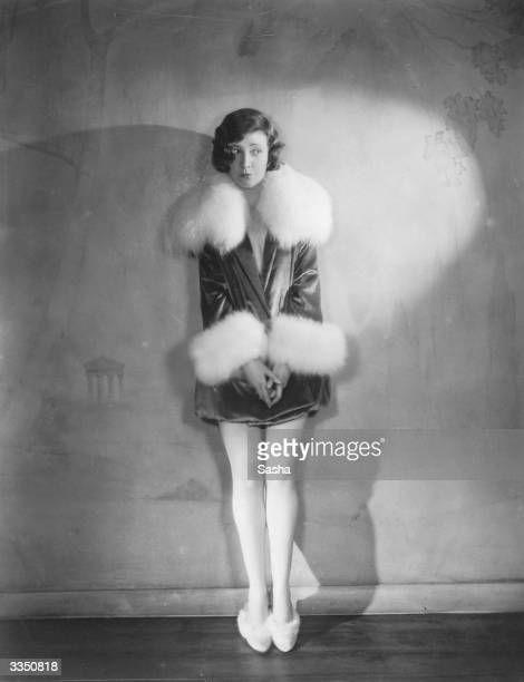 Actress Margaret Campbell wearing a fur-trimmed outfit with matching slippers.