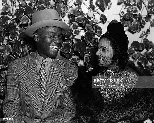 Bill Robinson the American tapdancer and entertainer renowned for his stairway dance is sitting sharing a joke with a friend at the Trocadero cafe