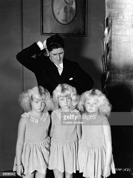 Director Edward A Sutherland appears confused by the Mawby triplets Claudette Angela and Claudine who appeared in a scene from 'The Baby Cyclops'