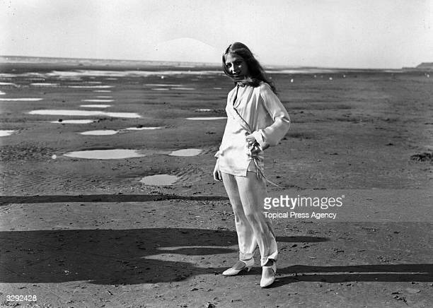 Evelyn Holt, the young actress, is standing on the beach at Blackpool, wearing a silk pyjama bathing suit, after her day's work filming of 'Three...