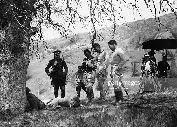 Gilbert Roland formerly Luis Antonio De Alonso the leading man is central with Henry King the director lying on the ground and Arnold Kent in uniform...