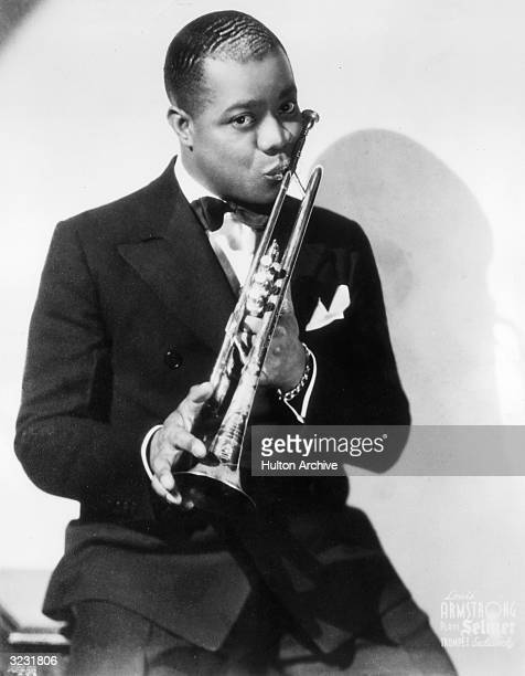 Portrait of jazz musician and actor Louis Armstrong kissing his trumpet.