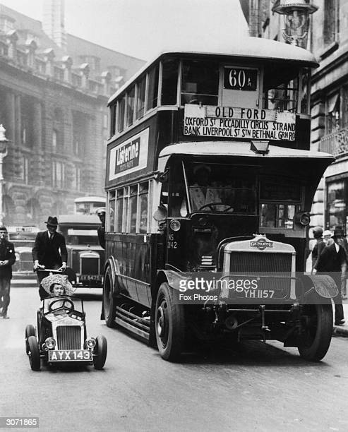 A bus and a midget car in a London street