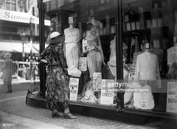 A passerby window shops for lingerie at a department store possibly Harrods of London during their Great Summer Sale