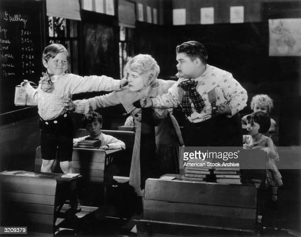 A teacher prevents child actors Harry Spear and Joe Cobb from fighting in a classroom in a still from one of producer Hal Roach's 'Our Gang' films...