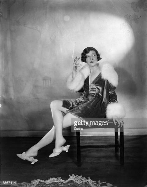Actress Margaret Campbell, wearing a fur-trimmed outfit with matching slippers, smoking a cigarette.