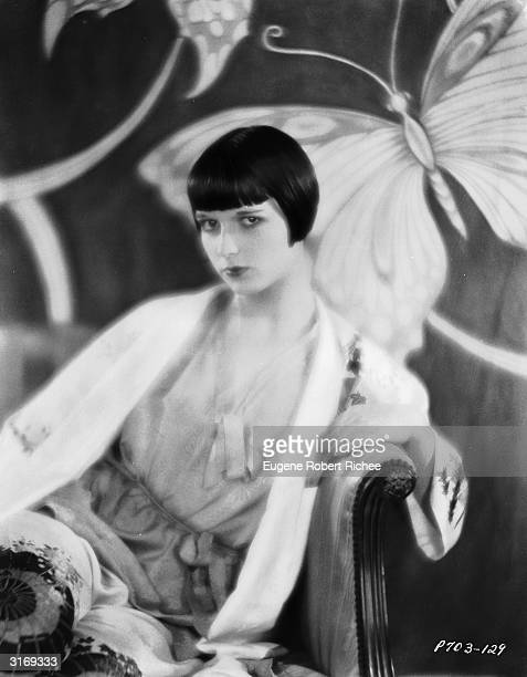 American actress Louise Brooks sitting on an armchair in front of a screen decorated with butterflies