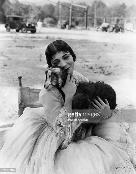 American actress Renee Adoree hugs a kid goat the mascot on the set of the film 'Tide Of Empire' directed by Allan Dwan for MGM