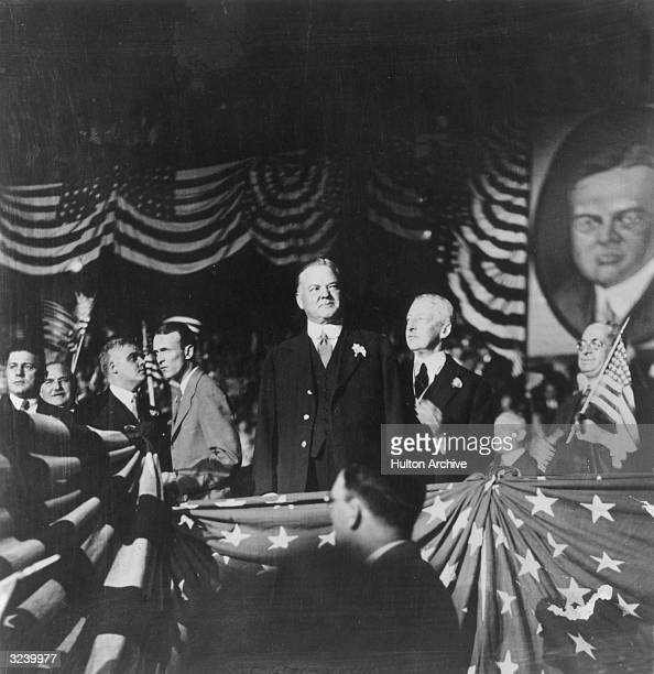 American politician Herbert Hoover campaigns for president from a platform decorated with U.S. Flags and banners.