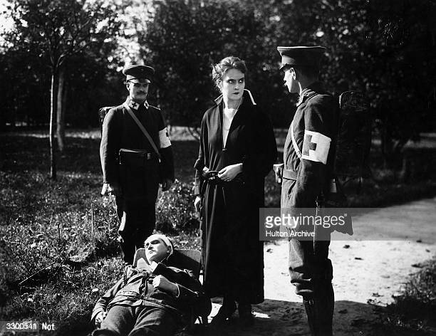 An injured man and red cross officials in a scene from the film 'Volk In Not'