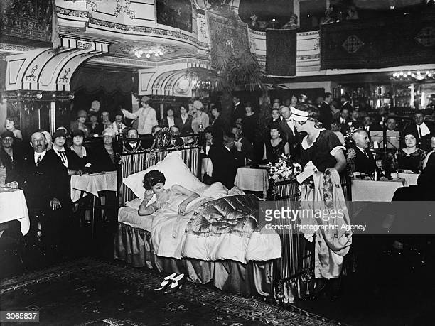 At a fashion exhibition in Berlin a masked woman lies in bed while a maid stands nearby with her clothes