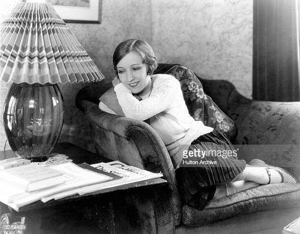 Bessie Love the Hollywood actress who appeared in 'Dress Parade' curls up in a chair in her Hollywood home