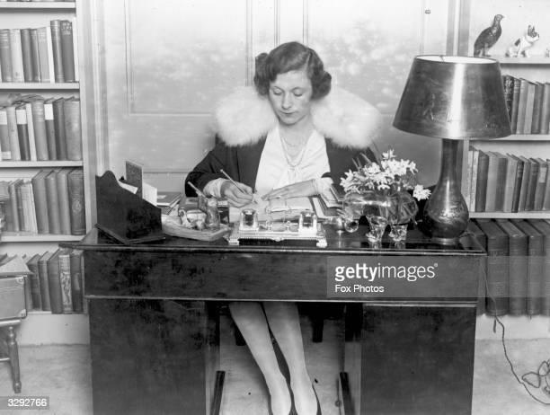 British romantic novelist Barbara Cartland at her desk.