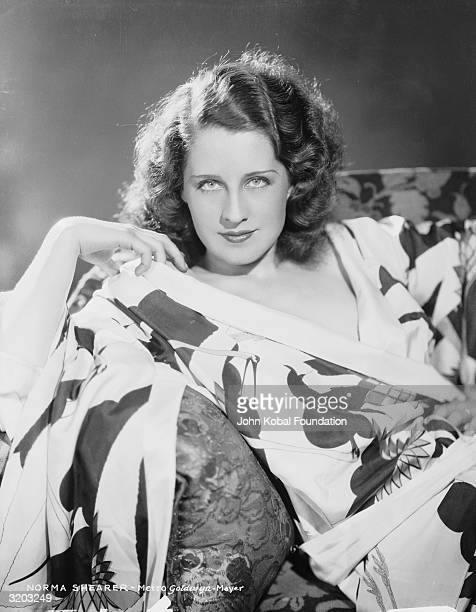 Canadian actress Norma Shearer lounges on a sofa in a floral patterned dressing gown