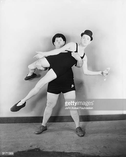 Dressed in leotard and bowler hat Stan Laurel is lifted by Oliver Hardy in a display of balletic refinement