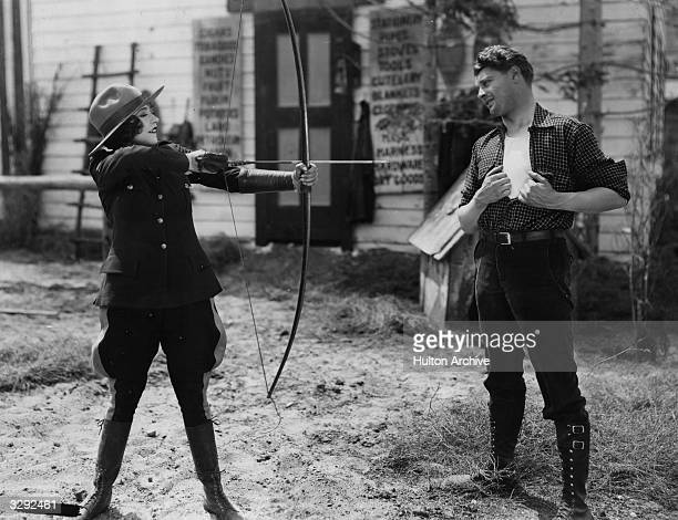 French actress Renee Adoree wearing a Mountie's uniform and practising archery for scenes in the first version of MGM's 'Rose Marie'