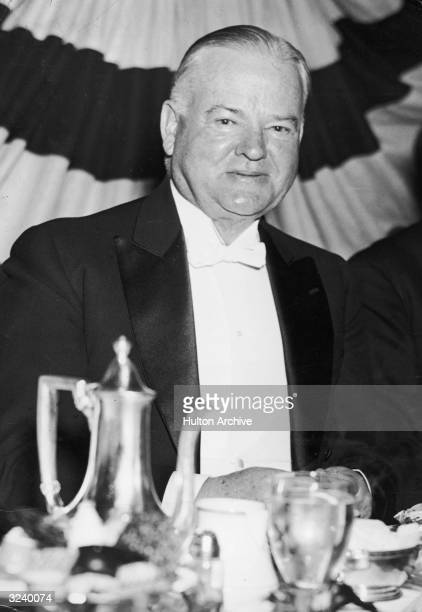 Headshot of American president Herbert Hoover sitting at a dining table in a white tie and tails.
