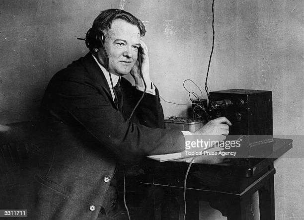 Herbert Hoover , Republican Party candidate for the Presidency of the United States of America, listening to a one valve radio set.