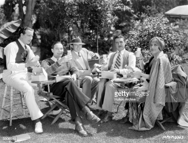 King Vidor the American director with John Gilbert the leading man and Aileen Pringle join William Haines in a snack between filming scenes of his...