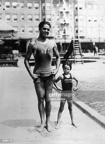 Malcolm McGregor the American swimmer and film actor is viewed with his young daughter by the side of an open air pool in California