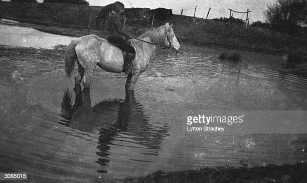 Painter Dora Carrington riding her horse 'Belle' near Ham Spray the home she shared with Lytton Strachey in Wiltshire