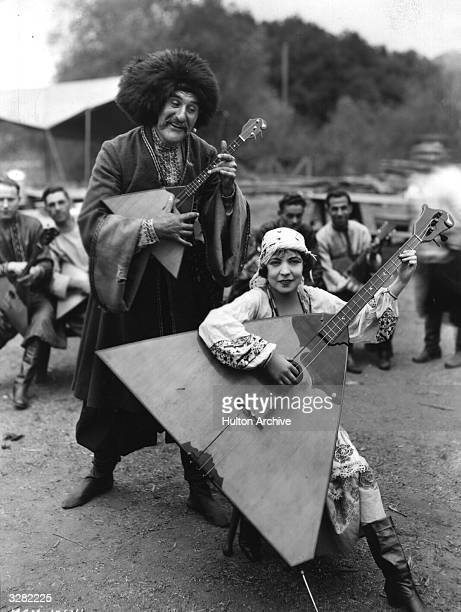 Renee Adoree and Ernest Torrence stars of MGM's 'The Cossacks' playing a pair of mismatched balalaikas during filming The film was directed by George...