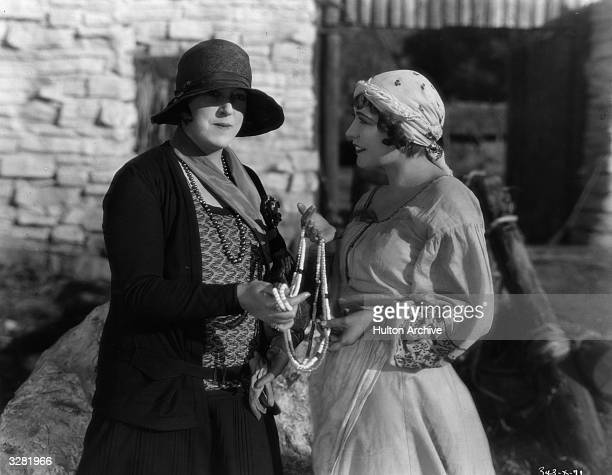Renee Adoree poses with journalist and photographer Margaret Chute on the set of the MGM film 'The Cossacks' directed by George W Hill and Clarence...