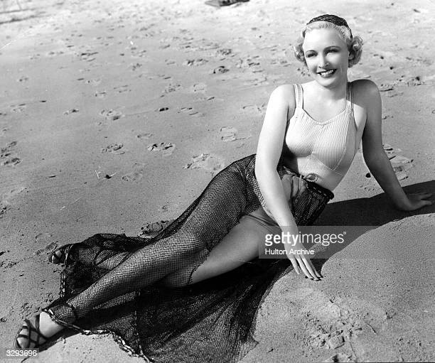Wearing a satin and lastex top and a skirt made of fishnet Ann Evors a Paramount player poses for the cameramen on the beach