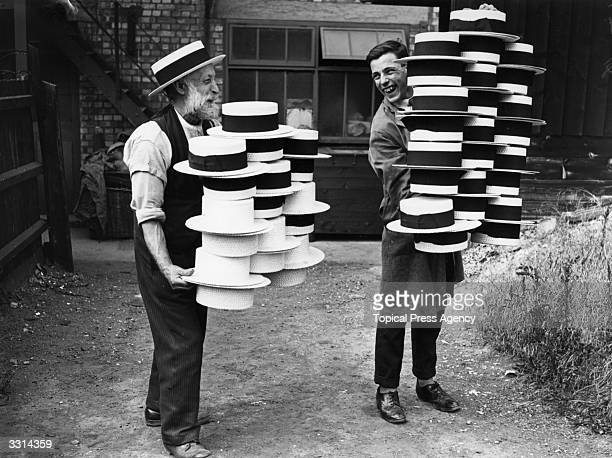 Workers at a hat manufacturers in Luton carrying piles of men's straw hats which were in demand due to a heatwave