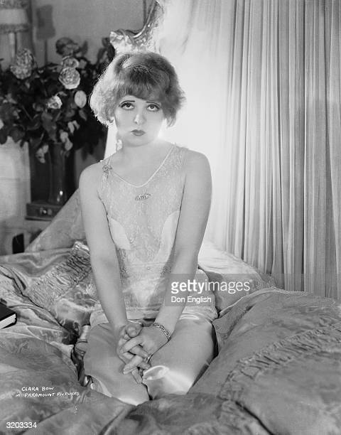 A sadlooking Clara Bow sits on a luxurious bed with draperies